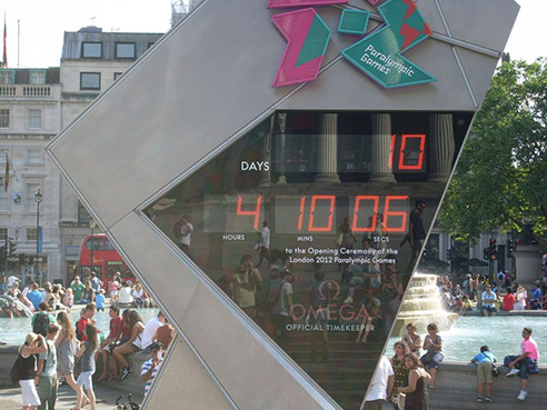 A screen in Trafalgar Square counts down to the Paralympic Games: 10 days, 4 hours, 10 minutes, 6 seconds. People sit by the fountain behind it.