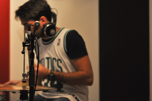 A young man in a recording studio - a microphone and drums in the foreground. He sits in the background with headphones on, out of focus.