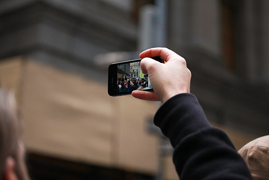 A man's hand holding a mobile phone up in the air. On the screen of the phone is a crowd of people in the street.