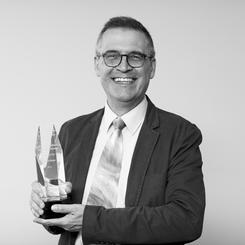 Black and white photo of Professor David Rowe holding his award (glass, engraved)
