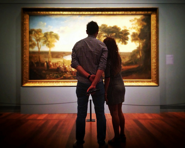 A man and a woman look at a landscape painting, with their backs to the camera.