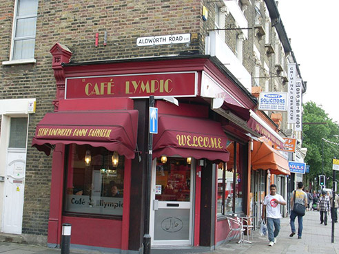 A red cafe's sign reads 'Cafe lympic'. The 'O' is missing.
