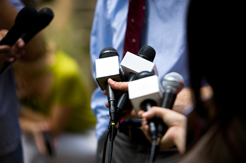 The hands of journalists holding microphones towards a man in a shirt and tie (face not visible).