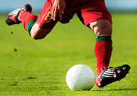 Shows the legs of a soccer player who is about to kick a soccer ball.