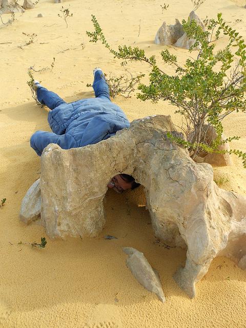 Jen Li laying on the desert inspecting a big rock