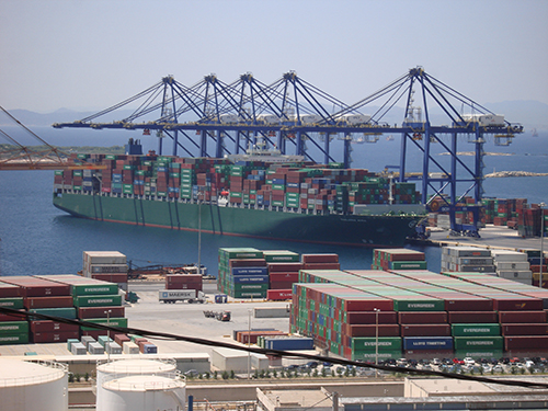 A ship loaded with shipping containers sits at port.