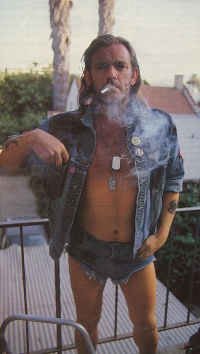 Lemmy wearing denim shorts and jacket with smoke