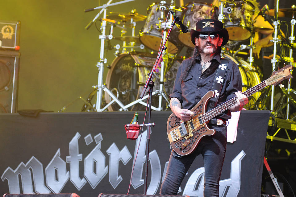 Rocker Lemmy standing with an electric guitar before a microphone