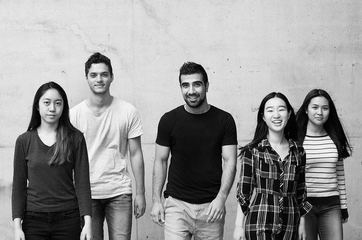 black and white photo of 5 students standing by a wall