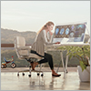 Thumbnail image of woman at a computer with outdoor view behind her.