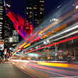 Thumbnail image of city at night with streaming lights of a bus in movement.