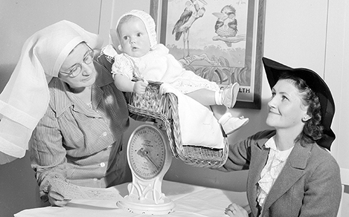 A nurse weighs a baby in Glen Innes, New South Wales, 1948.