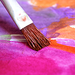 A brush painting bright colours on paper. Image by Uwe Baumann from Pixabay.