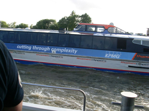 A boat on the river has 'cutting through complexity' printed on its side.