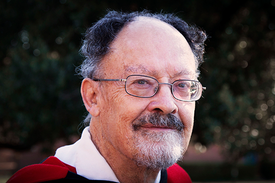 Close-up photo of Professor Bob Hodge from the shoulders upwards, wearing a graduation gown.