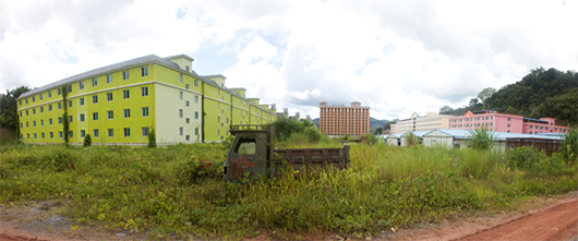 An abandoned truck and overgrown grass surrounds large buildings.