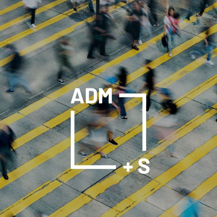 Approximately two dozen pedestrians walk in all directions across concrete which has yellow stripes painted diagonally across it. The figures are blurred and indistinct, indicating movement. The logo for the Centre for Excellence for Automated-Decision Making and Society is super-imposed on this image. The logo is a white box with the characters ADM+S on its perimeter.