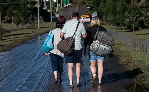 People walking away from floods with belongings, view from their back