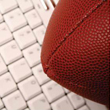 A brown rugby ball sitting on top of a white keyboard.