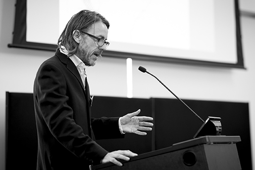 A black and white photo of Professor Donald McNeill presenting.