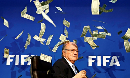 Sepp Blatter sitting with dollar bills falling down above and around him.