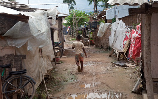 A young boy walks along a muddy path between roughly constructed shelters with large sheets of plastic hanging from them.