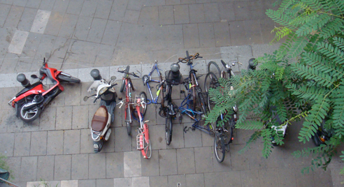 Looking down on some bikes and scooters on the pavement, some which have fallen over.
