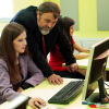 Teacher helping young female sitting by the desk in a computer lab