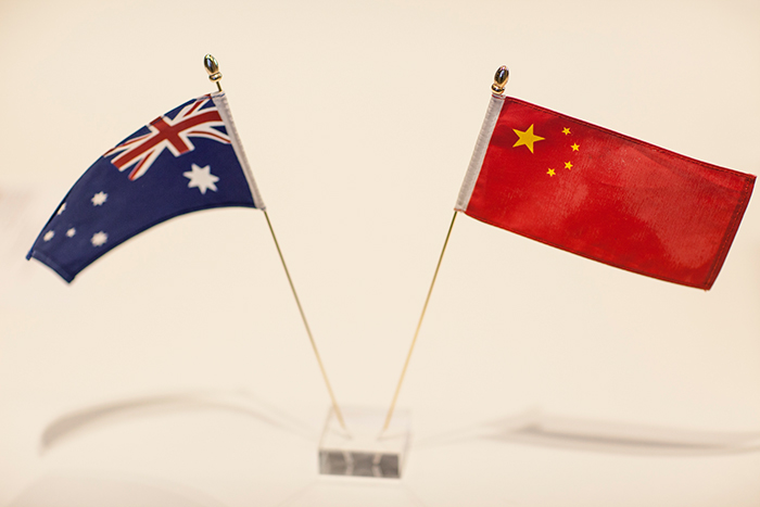 Two miniature flags leaning out of a small clear stand: an Australian flag and a Chinese flag.