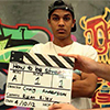 Thumbnail image of a young man behind a clapperboard and in front of a mural