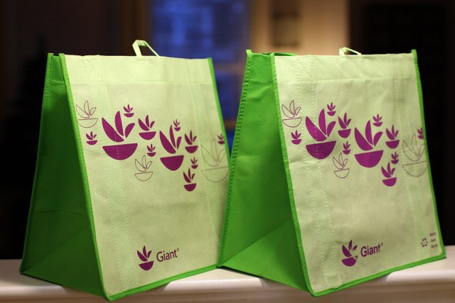 Two green reusable bags with a purple printed pattern on them.