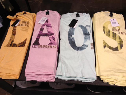 Four piles of t-shirts on a display table, arranged in a row so that the letters on them spell Laos.