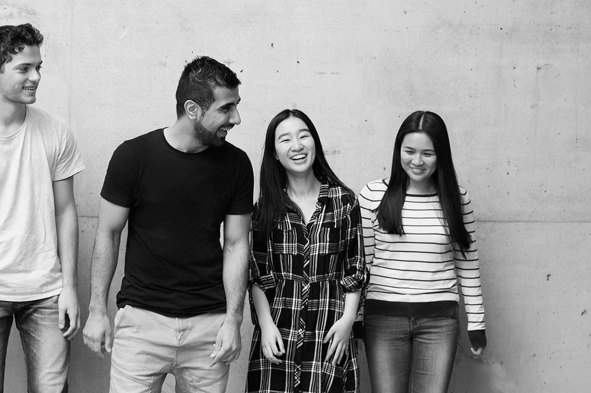 black and white photo of 4 students laughing