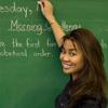 School teacher writes on the chalkboard