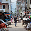 Thumbnail image of a young man walking through a street in a slum