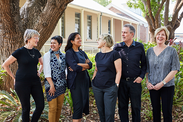 Kay Anderson, Malini Sur, Shanthi Robertson, Megan Wakins, David Rowe and Deborah Stevenson stand beside the Institute for Culture and Society building, beneath trees.
