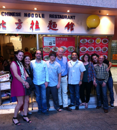 A group of nine people, including James Arvanitakis, stand in front of a Chinese Noodle Restaurant.