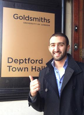 Kev Dertadian stands in front of a Goldsmiths University sign
