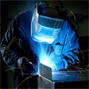 A man welding with blue sparks coming of the metal