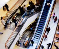 People travelling up and down escalators at a mall.