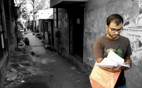 A man stands in a narrow alleyway looking at a stack of papers in his hand. He is pictured in colour. The alleyway is in black and white.