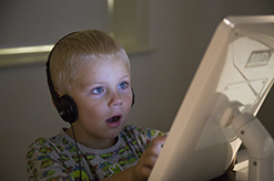 Young boy wearing headphones and looking at iPad screen