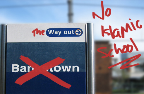 A Bankstown station sign which has been written over in red writing now reads 'No Islamic school'.