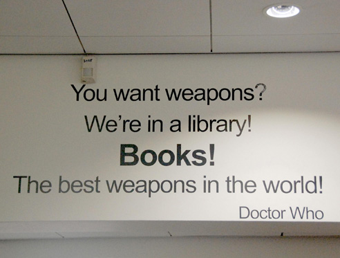 A Doctor Who quote on the wall of a library reads: 'You want weapons? We're in a library! Books! The best weapons in the world! Doctor Who'.