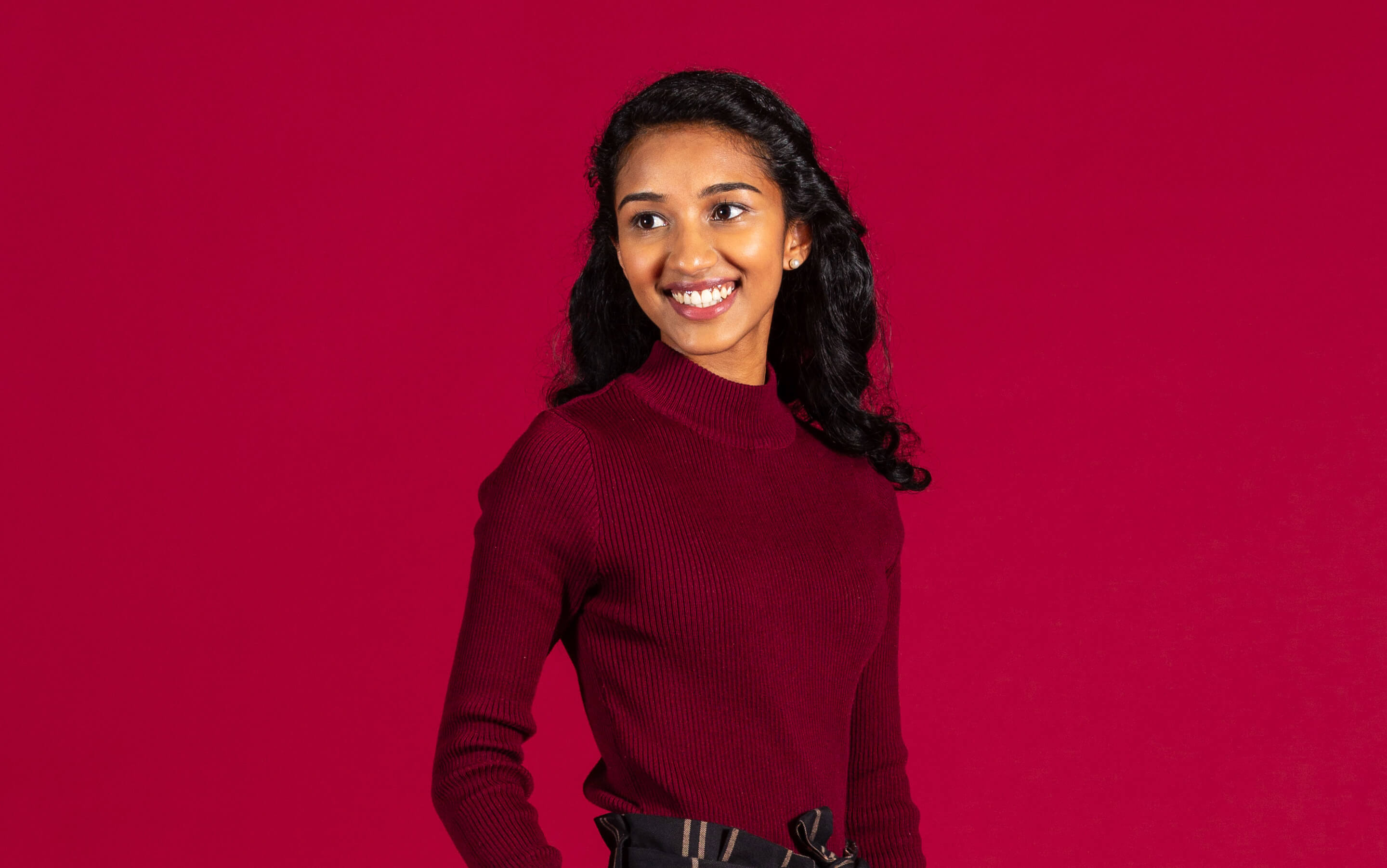 Student smiling with crimson background