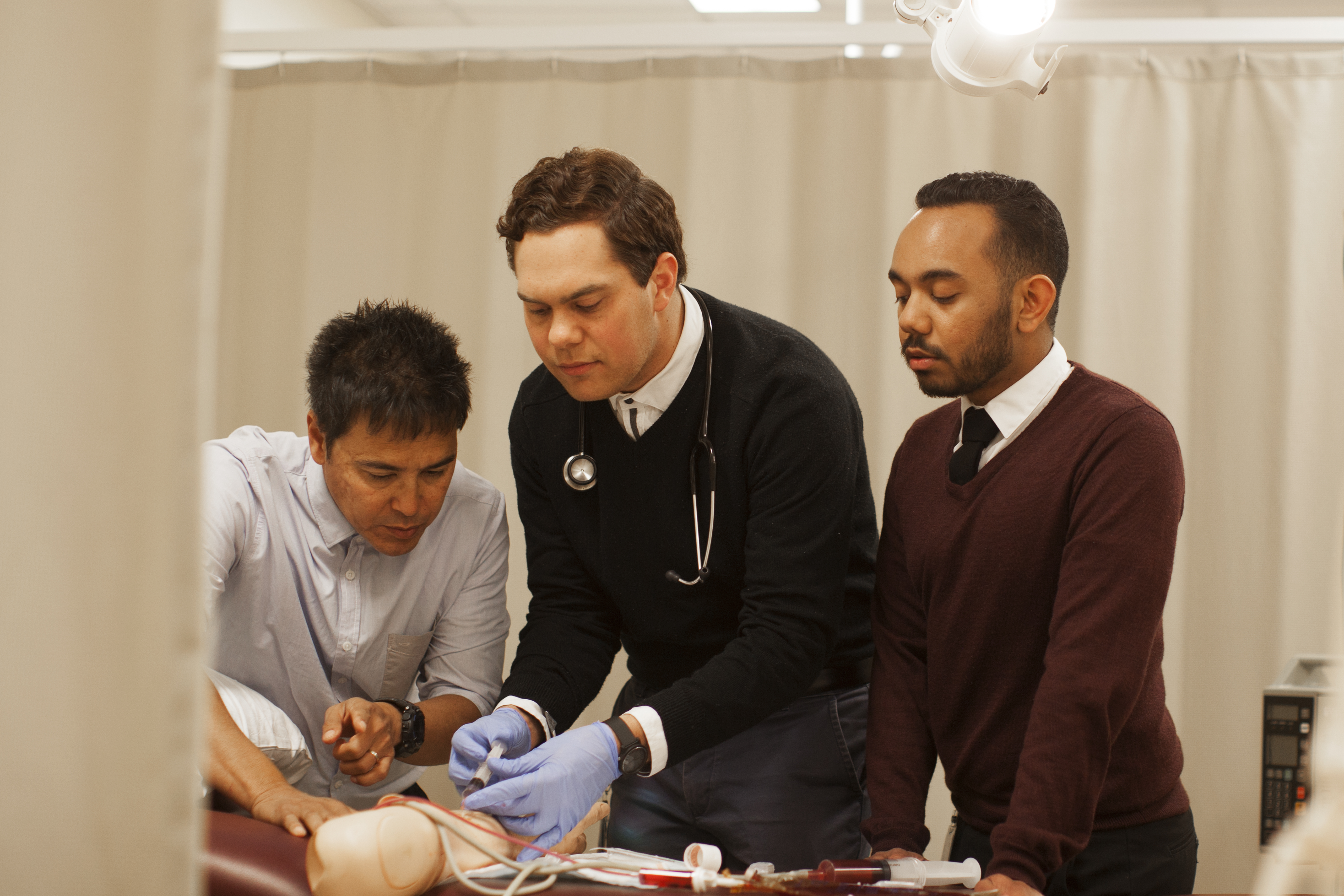 Three medicine students working in a simulated clinical workplace