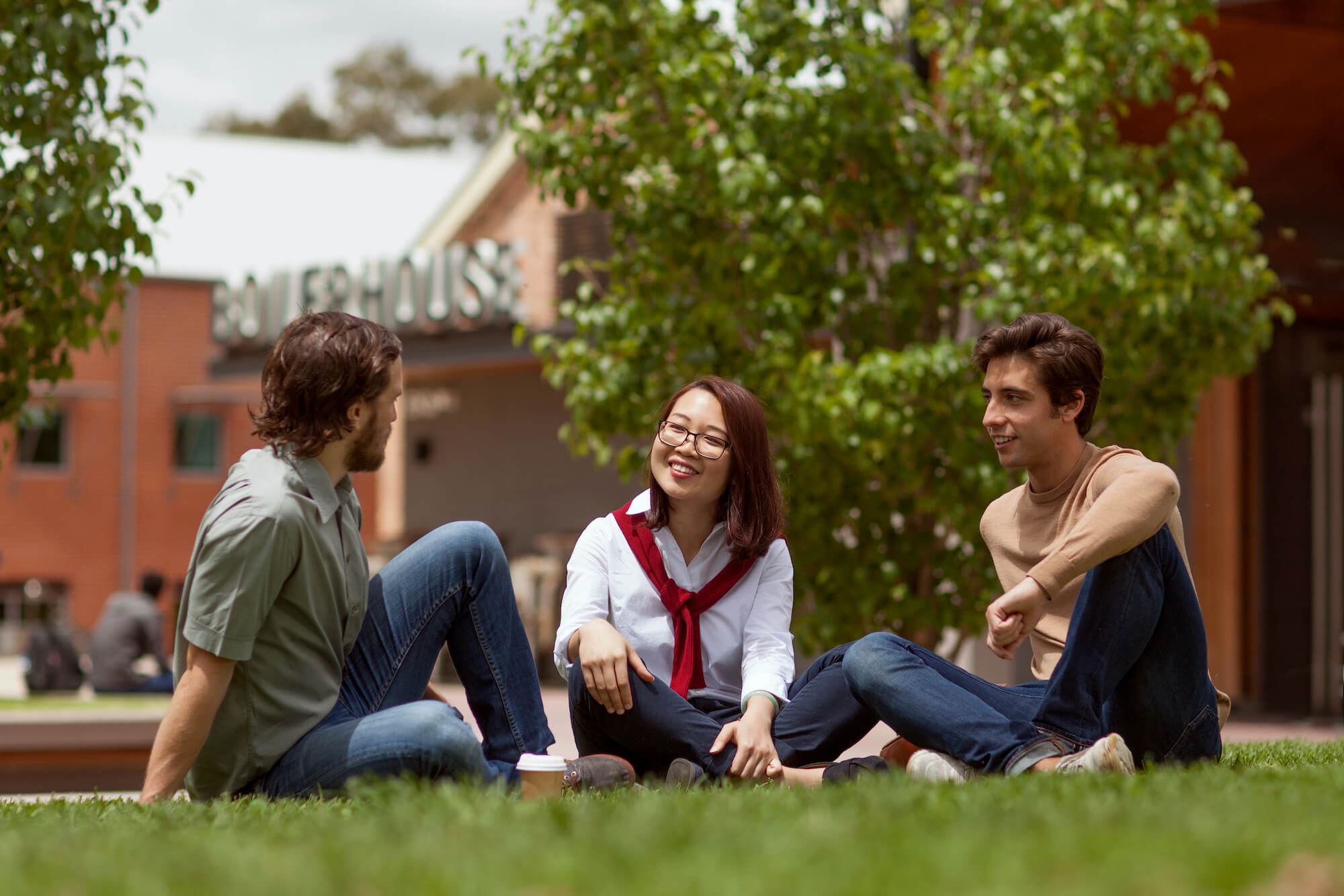Three students sitting together on the grass at WSU Parramatta South campus
